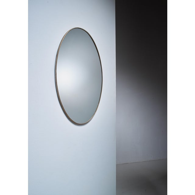 A very elegant, oval brass Italian wall mirror with minimal old brass frame.