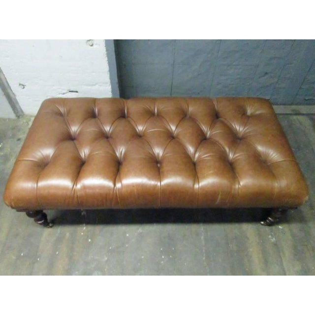 English tufted leather bench with brass casters. George Smith.