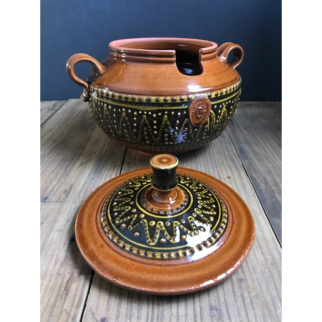 Exceptional hand glazed ceramic serving bowl with statuesque lid. This piece carries an oval embossed insignia on one side...