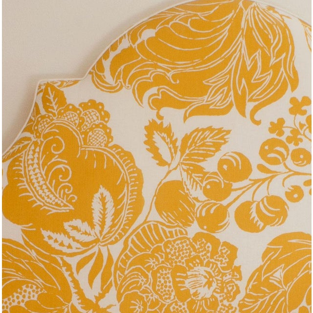 This queen sized headboard is upholstered with a striking yellow and white floral fabric and accentuated by white welting.