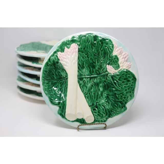 A set of seven hand-painted footed ceramic salad or snack plates with embossed white asparagus and green cabbage leaf...