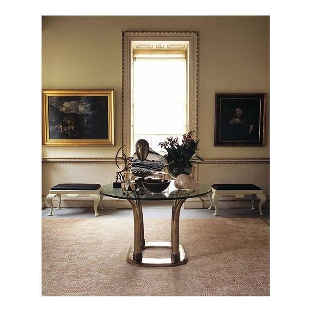 Supported by a brass base composed from four ribbed and textured inverted tusks mounted on a flat floor plate.