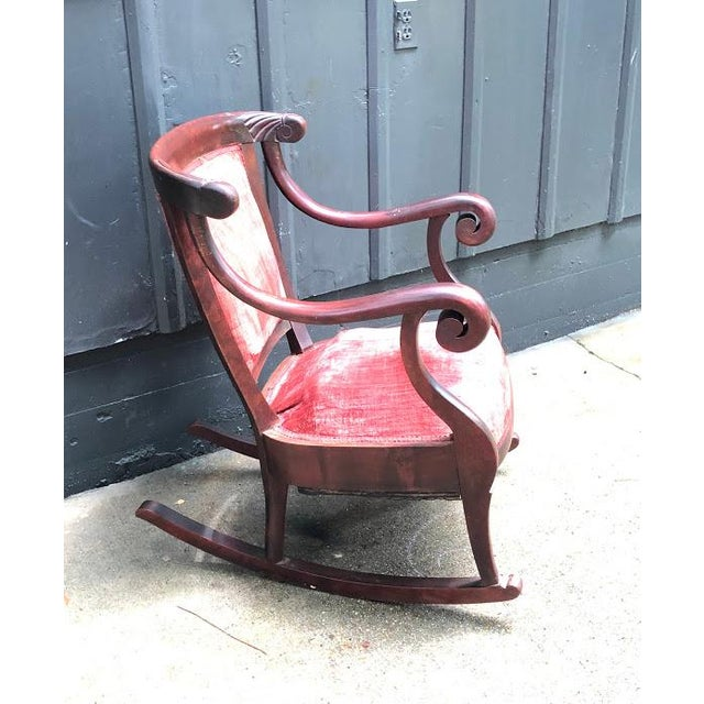 Vintage 1920s-30s carved wood/burgundy velvet rocking chair. Some minor fading to velvet fabric and a couple of cracks in...