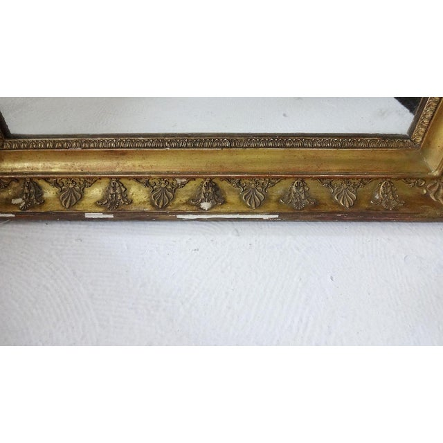 A late 19th Century, French gold-gilded mirror with decorative design. There is slight losses to the gilding.
