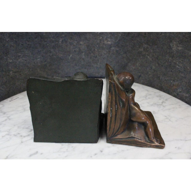 Two bronze bookends depicting children leaning as if to hold up the books.
