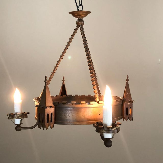 Antique Gothic Wrought Iron Chandelier lends a rustic air yet is charming with its parapets mounted between the arms that...