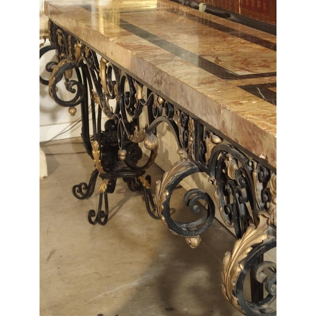 This is a fantastic, narrow and long console table made from forged iron and a slab of thickly veneered variegated marble....