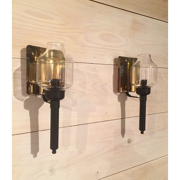 """Pair of wall sconces with brass reflectors, glass hurricane shades and metal """"push-up"""" candle holders by Ystad, Sweden,..."""