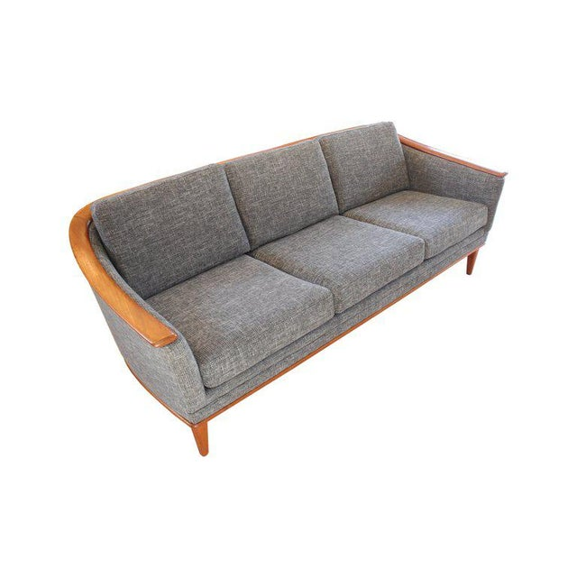 Mid-century modern sofa with continuous wood back and arm, and wooden platform base and legs, 1960s. Fully and...