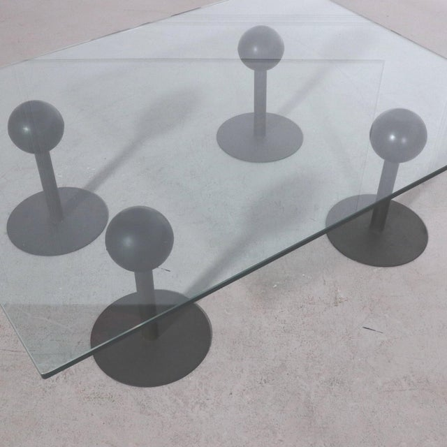 Rare coffee table, designed by Philippe Starck in 1982 for Les Trois Suisses. This table was made of 4 black metal bases...