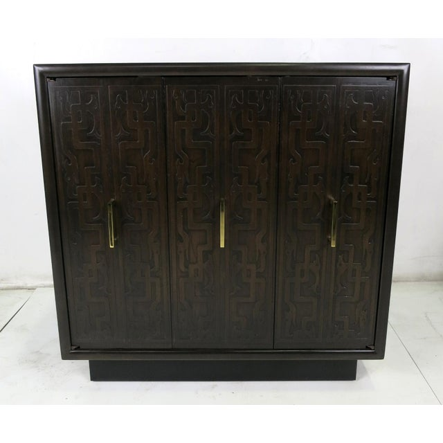 Fine pair of bedside cabinets with embossed Tribal design doors. One pair of doors on each cabinet is a bi-fold type along...