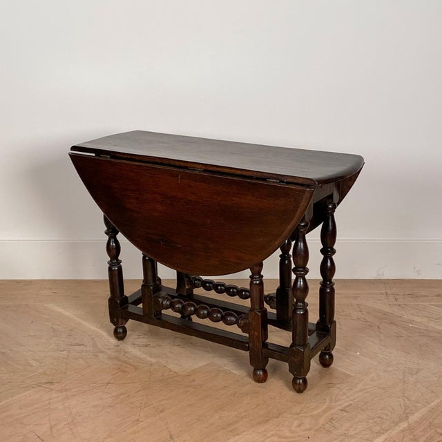 A nice scale 19th Century oak drop leaf table with nice turned legs and good patina, England. When opened the table...