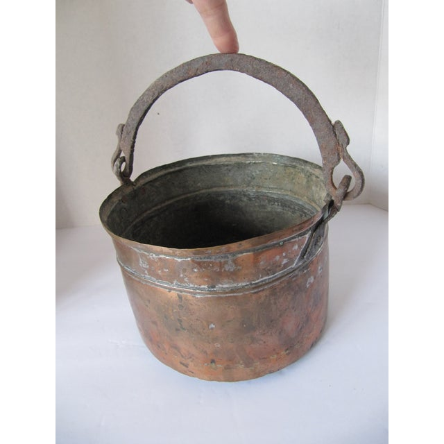 Antique handmade copper pot with rusty iron handle. This piece is well worn and the inside has a lot of corrosion, no...
