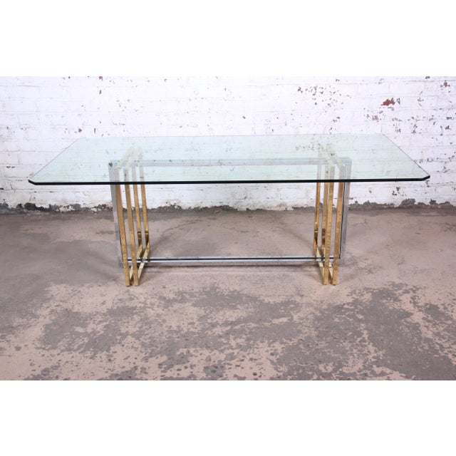 A gorgeous Romeo Rega style Hollywood Regency dining table in brass, chrome, and glass. The table features a unique...