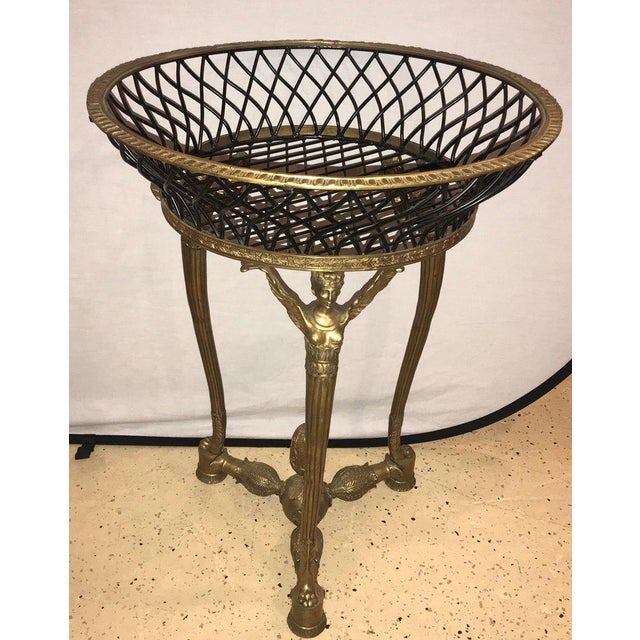 A 19th or early 20th century Empire bronze basket or jardinière on figural gilt bronze stand. The bronze framed ebony...