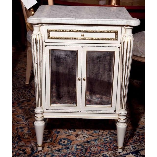 Pair of French white painted and distressed cabinets, circa 1950s. The white marble over a conforming case fitted with a...