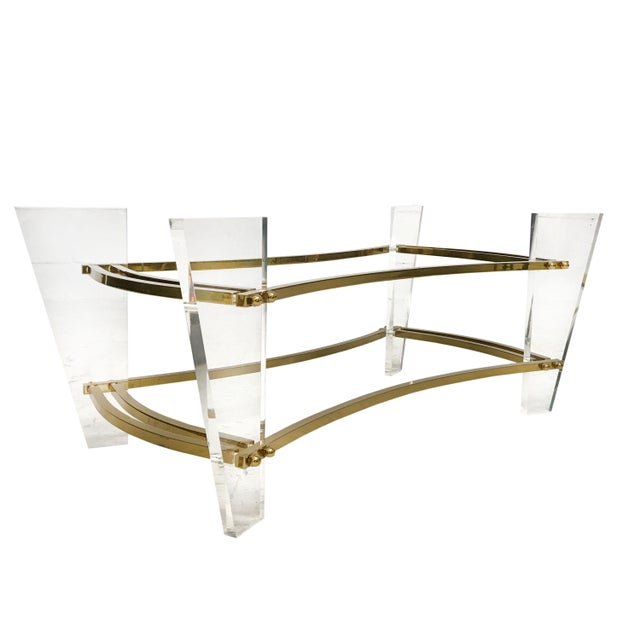 Mid Century Hollywood Regency style cocktail table in brass and lucite. Very good condition with age appropriate wear....