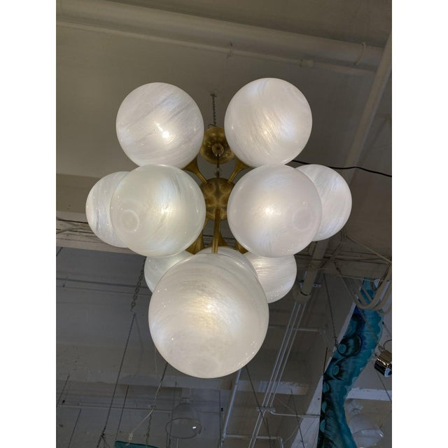 Design Plus Gallery presents a Visual Comfort Cristol Tiered Chandelier. Features ten glass sphere shades which hang in...