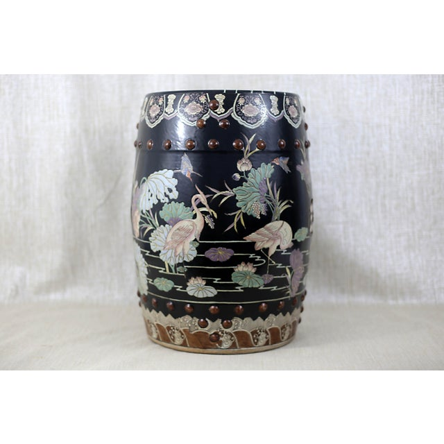 A beautiful and unusual hand-painted ceramic garden stool, with a matte black finish and scenes of cranes and other birds...
