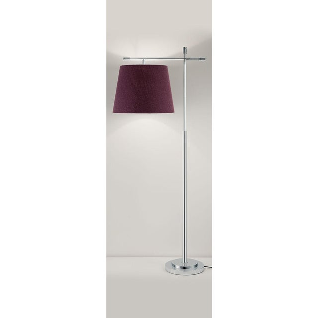 A polished chrome metal work lamp with a linen shade. Stepped base supports crossed columns with decorative end detailing....