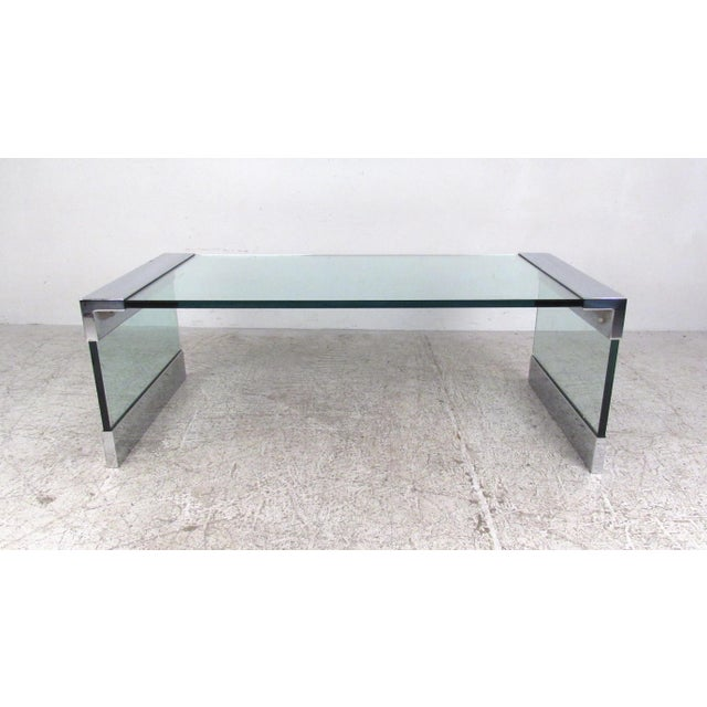 This uniquely angular coffee table features impressive Mid-Century style with quality chrome and glass construction. Thick...
