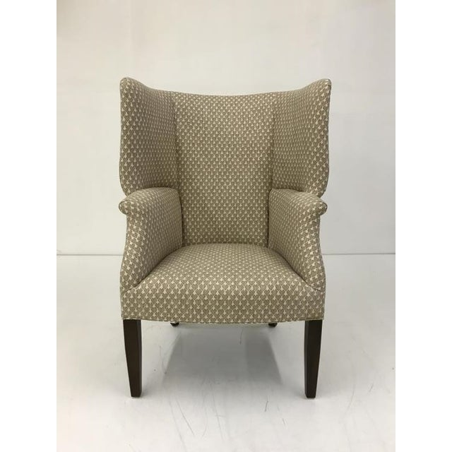 The Andre Chair is a first quality showroom sample that features a patterned beige fabric with a walnut finish.
