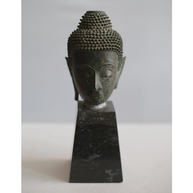 Collection of 11 mounted bronze Thai Buddha heads. Eight are mounted on marble and three are on wood including a hand....