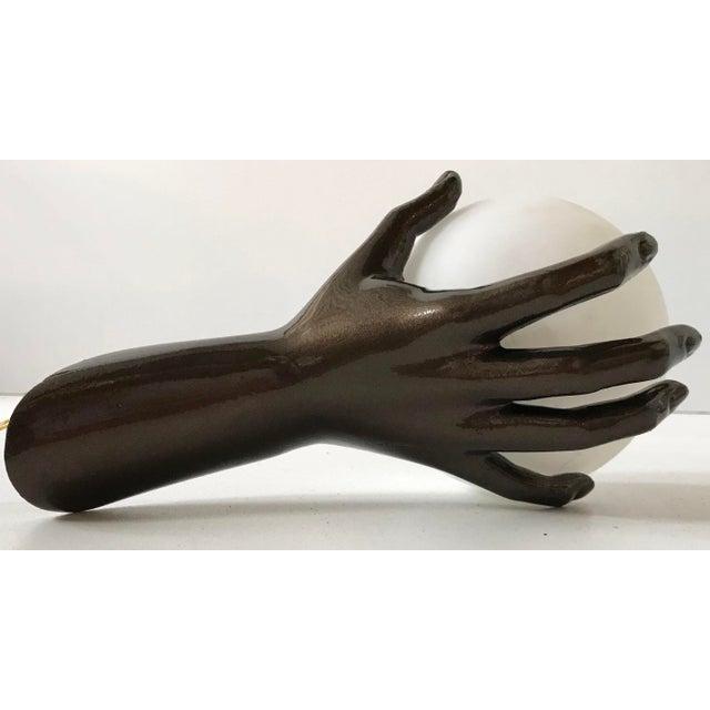 Fantastic Pair of Sconces by Maison Arlus, figuring a dark bronze hand holding an opaline glass globe Provenance: Parisian...