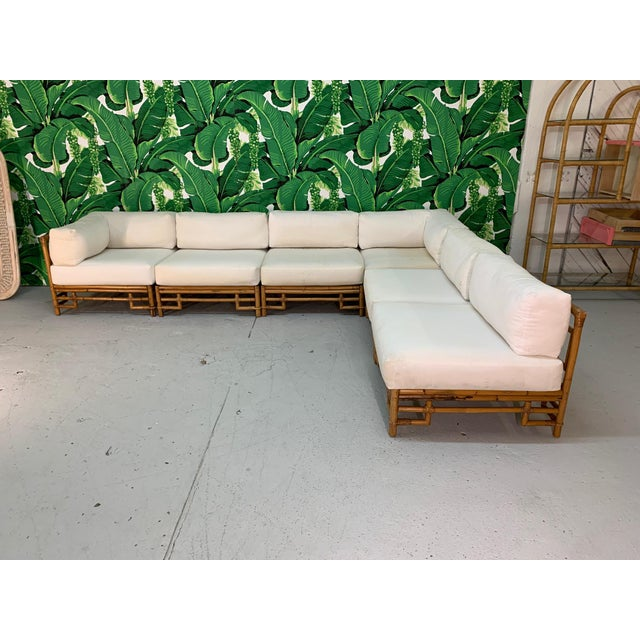 Large six piece modular sectional sofa by Ficks Reed features rattan frame and chinoiserie style design. Cushions are...