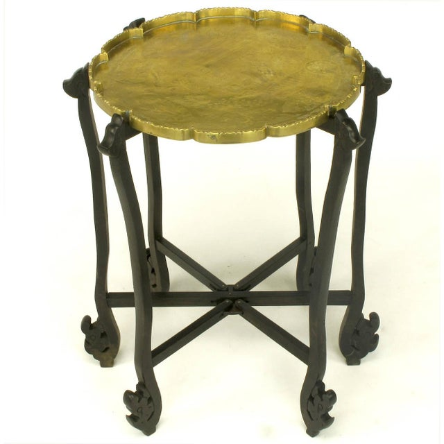 Exotic folding tray table of carved ebony wood with six legs that fold flat. Etched scene into thick brass tray with...