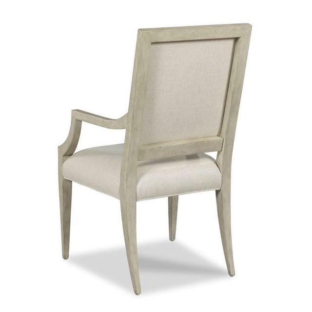 A upholstered back rests above an upholstered seat raised by tapering legs. Crafted from hardwood solids.