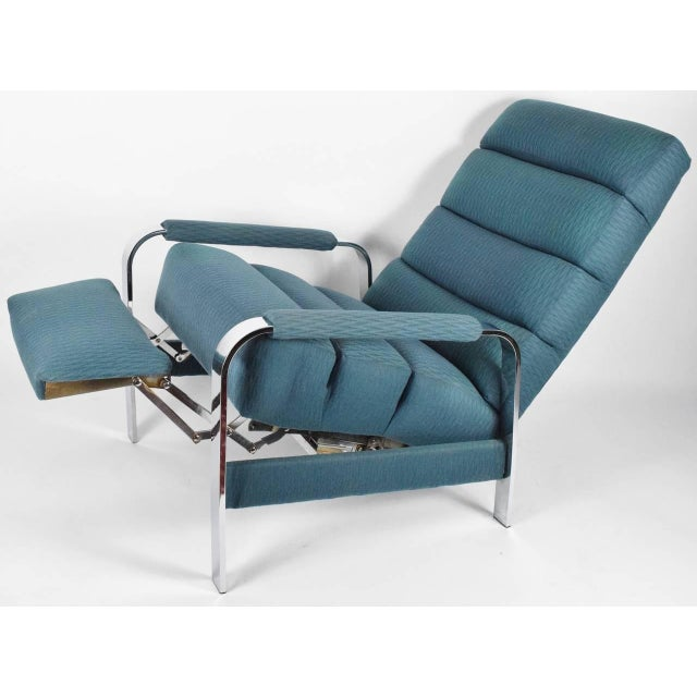 A mid century modern recliner designed by Milo Baughman and made by James Inc . A flatbar chrome frame with teal upholstery.