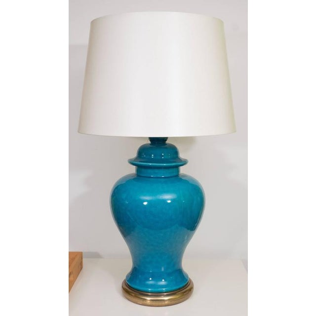 A stunning pair of ceramic urn lamps in a beautiful shade of blue on a brass base with cream colored drum shade.