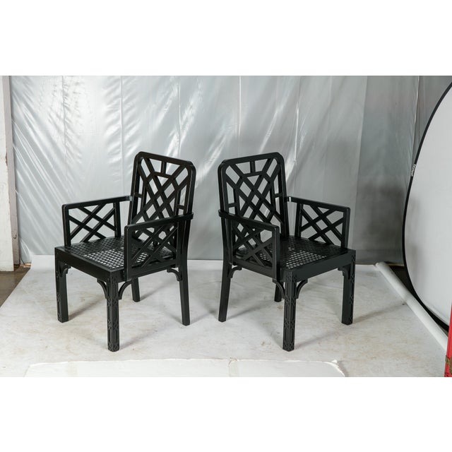 Vintage Madcap Cottage Chinese Chippendale-style wood side chairs with caned seats and fretwork backs and arms in a rich...