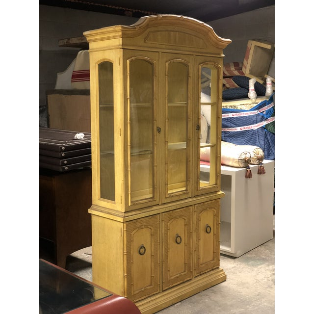 An faux bamboo china cabinet. This sunny yellow cabinet is detailed with a faux bamboo at the cabinet edge, crown, and on...