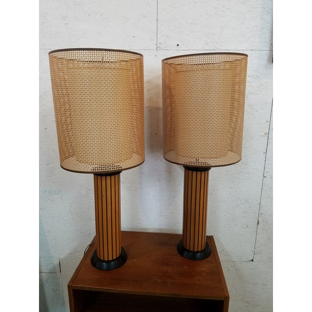 Pair of wood strip lamps with two piece solid inner and wicker outer shades. Designed by Hans Wegner. 36 in. tall, 5.5 in....