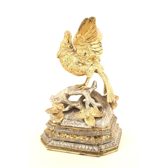 Pair of French Victorian silver and gilt plated metal birds standing among branches on a tiered rectangular base.