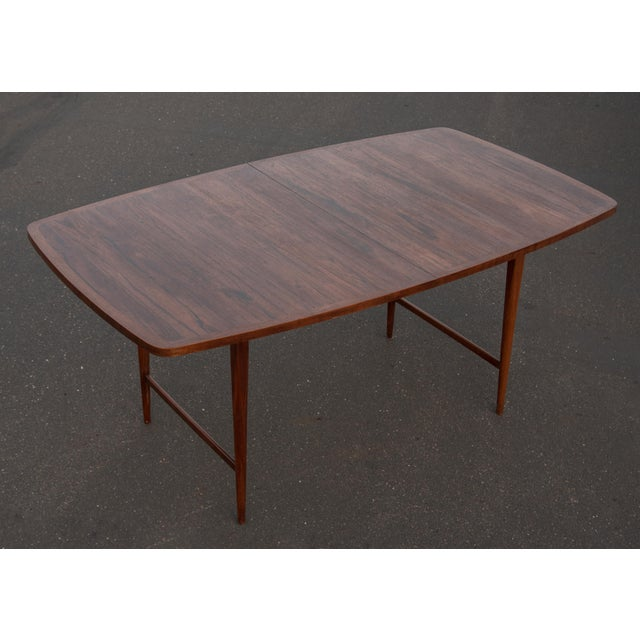 Paul McCobb Rosewood Delineator series dining table with walnut banded bowed sides and tapered legs. two 12 inch leaves...