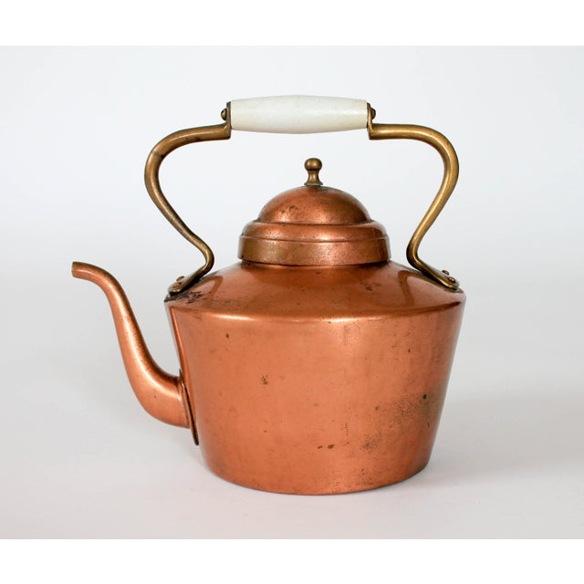Vintage copper and brass tea kettle with white wooden handle. Makers mark on bottom. Overall age wear. Recommend for...