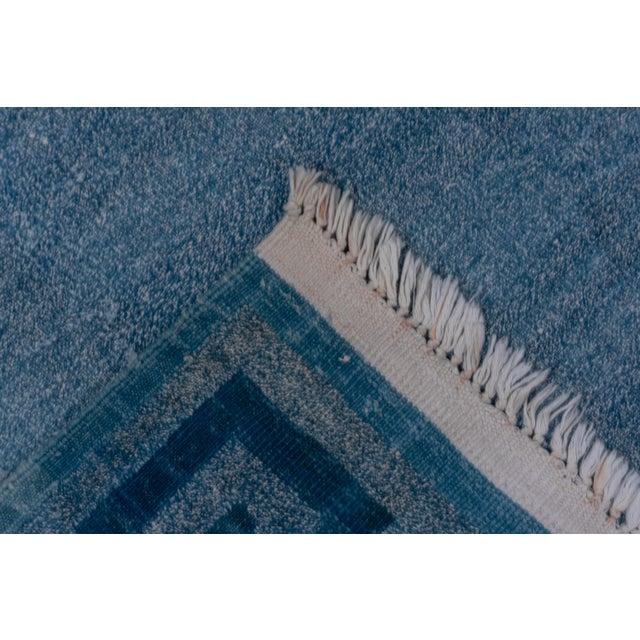 This modern call-cotton, tapestry weave flat carpet shows a dark blue Greek key pattern neatly framing the plain light-...