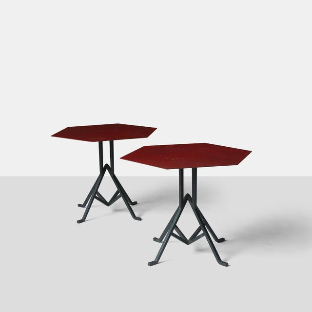 A pair of iron base coffee tables with a hexagon shaped metal top with the original red enamel finish. The metal base has...