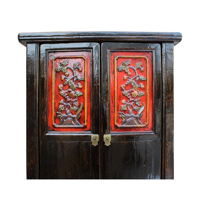 This is a tall slim storage cabinet with oriental relief carving of flower on the doors. The surface is finished with...