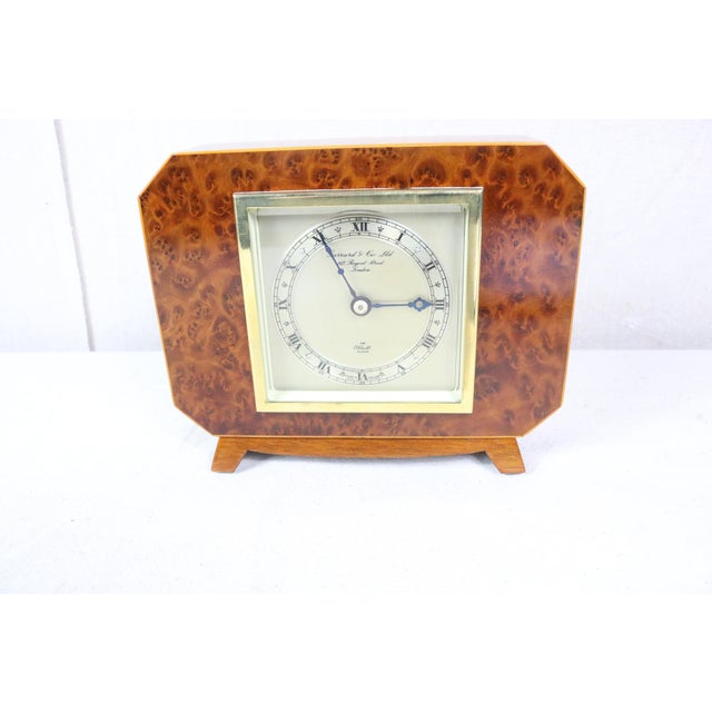 English Deco clock with a burl-walnut case, satinwood edge molding, beveled glass dial cover, silvered face, and original...