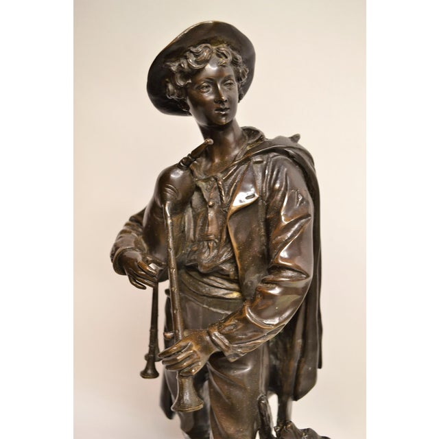 This is an appealing figural bronze of a man with his bagpipes and companion dog, begging for attention.