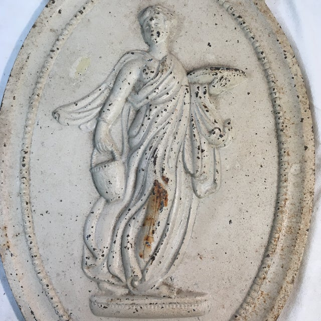 This cast iron plaque features a Neoclassical woman carrying a basket in one hand and tray in the other. She wears a thin...