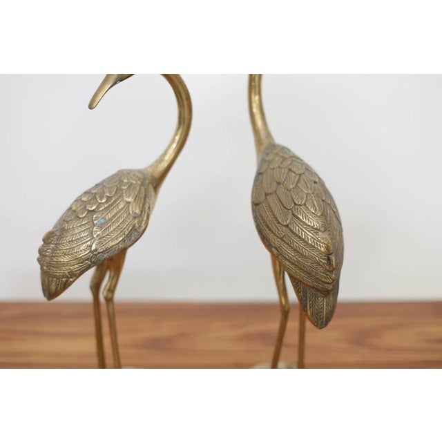Beautiful pair of flamingos or cranes made of brass. They are in very good condition and they bring the Hollywood Regency...