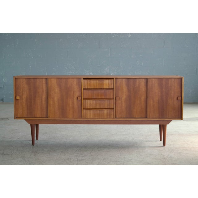 Beautiful Danish midcentury low sideboard in teak made by Domino Møbler in the 1960s. Nice center drawer section flanked...