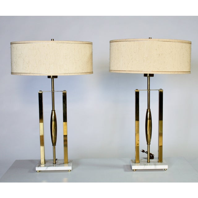 Pair of Mid-Century Modern brass and marble lamps with original cream color linen drum shade decorated in gold thread....