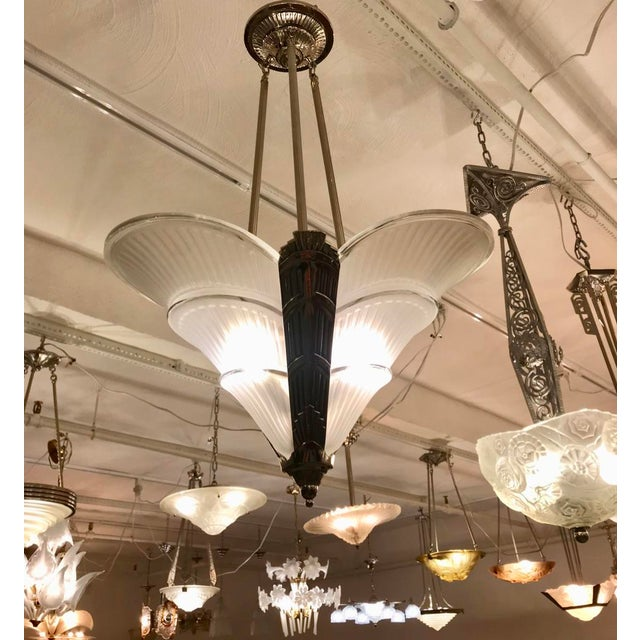 French Art Deco chandelier. Having three clear frosted glass panels having ribbed motif with polished details. Held by a...