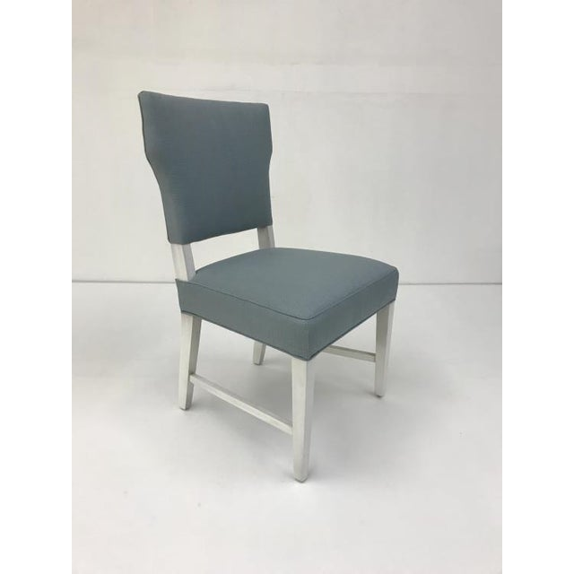 The Manset Dining Chair is a first quality market sample that features a Baby Blue Fabric with an Oyster Finish.